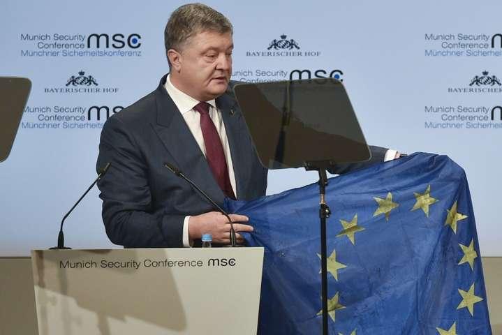 <em>Петро Порошенко демонструє прапор ЄС, привезений з Авдіївки</em>