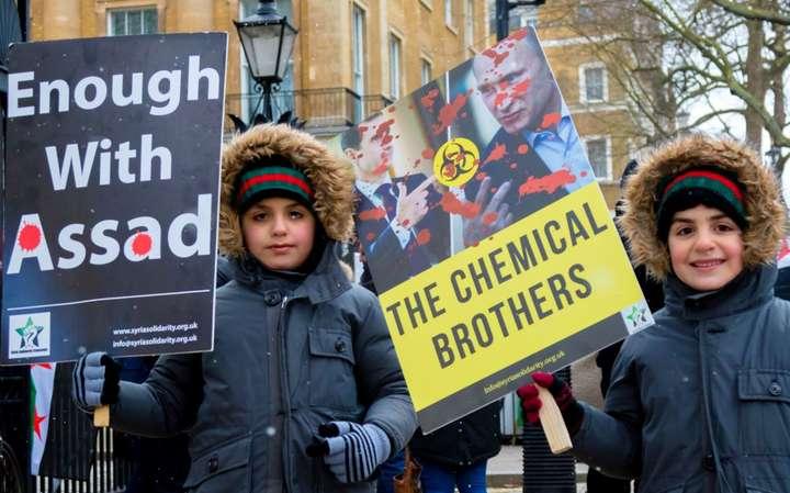 <span>Сирійські діти на акції протесту в столиці Великої Британії проти режиму Башара аль-Асада в Сирії та режиму Володимира Путіна в Росії. На акції був плакат із зображенням двох «хімічних братів» Асада і Путіна. Лондон, 17 березня 2018 року