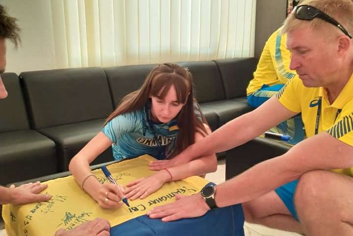 Олена Собчук, тренер В'ячеслав Тиртишник та інші атлети підписали для дипломатів український стяг