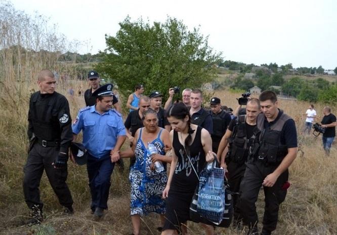 Правоохоронці виводять ромів Лощинівки після погромів, які влаштували місцеві селяни (фото: izbirkom.org.ua)