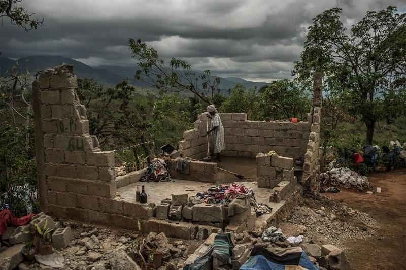 85-летняя Роза Дена пытается расчистить то, что осталось от ее дома после урагана «Мэтью» на юге Гаити.