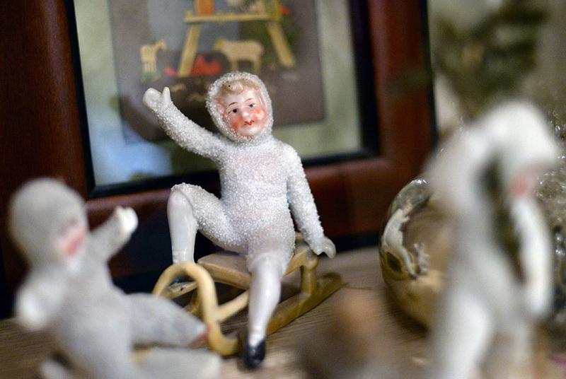 Дети на санках. Ватные игрушки с фарфоровыми лицами. Конец XIX — начало XX века Из ваты делали самые разнообразные фигурки: ангелов с крыльями, райских птиц, девочек на коньках и мальчиков на лыжах. Часто головки у этих куколок были фарфоровые. Также в магазинах продавались вырубные листы с хромолитографическими изображениями. Из этих листов можно было вырезать лица тех же ангелов, детей или дедов-морозов и приклеить на ватную или тканевую игрушку.