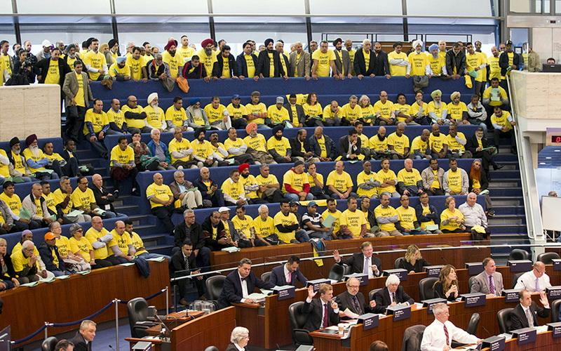 Демонстранты (в желтых футболках) слушают дебаты о внесении изменений в правила регулирования услуги такси в городском совете в Торонто, Канада, 30 сентября 2015 года.