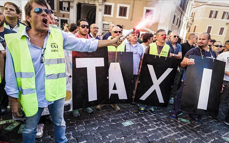 Итальянский таксист поджег фаер во время акции протеста против сервиса Uber в Риме, Италия, 10 сентября 2015 года. Сотни итальянских водителей такси вышли на улицы Рима в знак протеста против проекта закона в пользу сервиса UberPOP.
