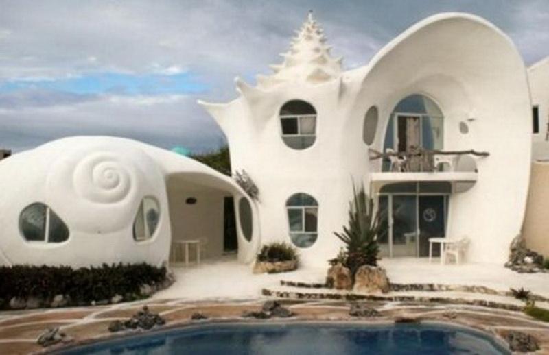 """Дом """"Ракушка"""" (Casa Caracol), остров Исла-Мухерес (Isla Mujeres). Губка-Боб Квадратные Штаны жил в ананасе на дне моря, так что имеет смысл и нам, людям, пожить в гигантской морской ракушке.   Дом """"Ракушка"""" является самым уникальным в Карибском бассейне и одним из самых креативных с художественной точки зрения в мире. Дизайн этого необычного дома разработал его владелец и по совместительству известный мексиканский художник-сюрреалист Октавио Окампо со своим братом-архитектором Эдуардо.   В процессе строительства использовались как цемент с бетоном, так и раковины, кораллы и другие природные переработанные материалы, найденные на пляже. Главной идеей стало желание создать дизайн, гармонично сочетающийся с окружающей средой и подчёркивающий природную красоту острова."""