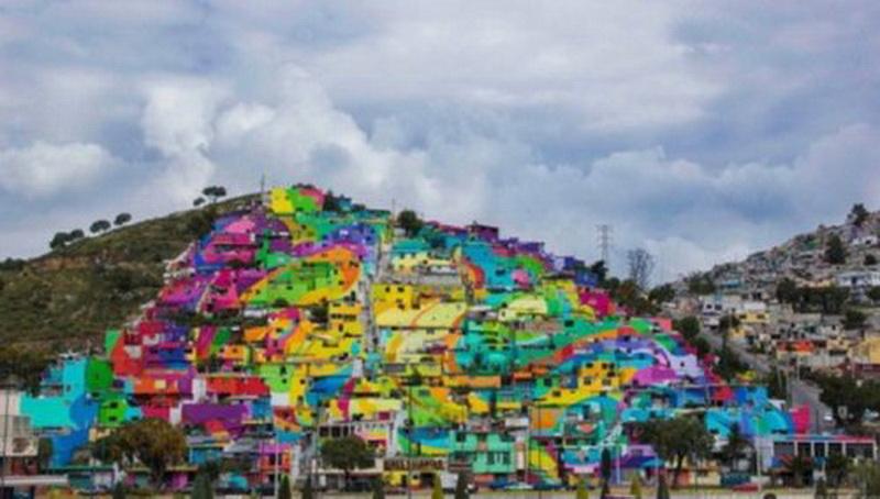 """Гигантский настенный рисунок в Палмитас (Palmitas), округ Пачука (Pachuca). Этот огромный настенный рисунок (возможно, один из крупнейших в мире) покрывает более 20.000; стен 209 домов общины Палмитас, а на его создание понадобилось 5 месяцев.  Проект, представляющий собой совместную работу правительства Мексики и молодёжи общины, объединившейся в организацию """"Germen Crew"""", был направлен на улучшение социальной жизни городка. Совместная стрит-арт работа привлекла участие членов 452 семей — 1808 человек!"""